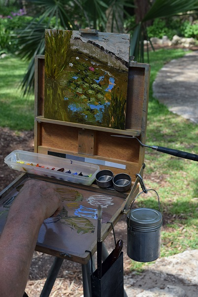 An artist painting the view of a lily pond