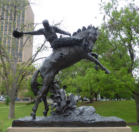 A bronco and a rider statue in broad daylight