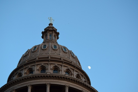 The Texas Capitol building with a half moon in the background
