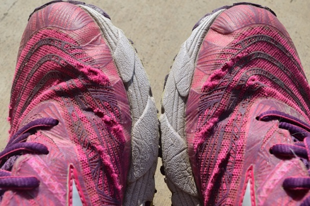 Pink running shoes that have holes worn through the tops