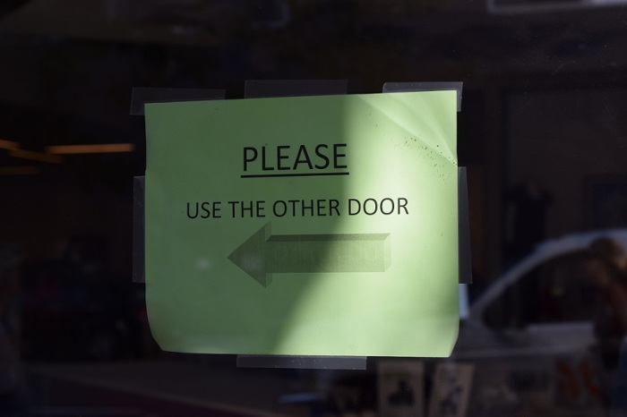 """Sign on door that says """"Please use the other door"""" and it has an arrow pointing to the left"""