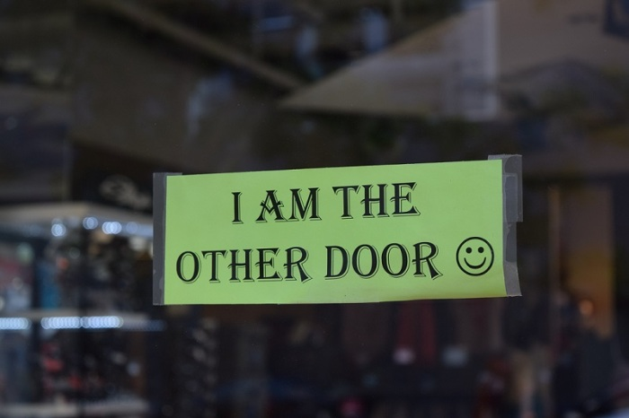 """Sign that says """"I am the other door"""""""