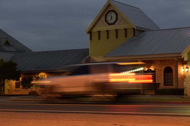 A photo of the Buda City Hall clock in focus and a vehicle driving by in a blur, which was the desired effect.