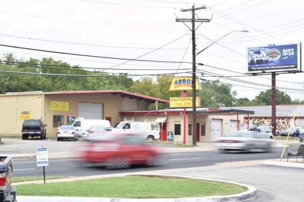 A blurred red vehicle driving by a yellow Auto Works sign and the sign is in focus.