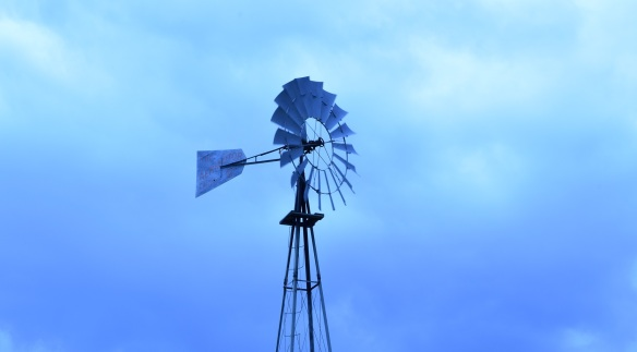 A windmill with purple, blue and lavender skies