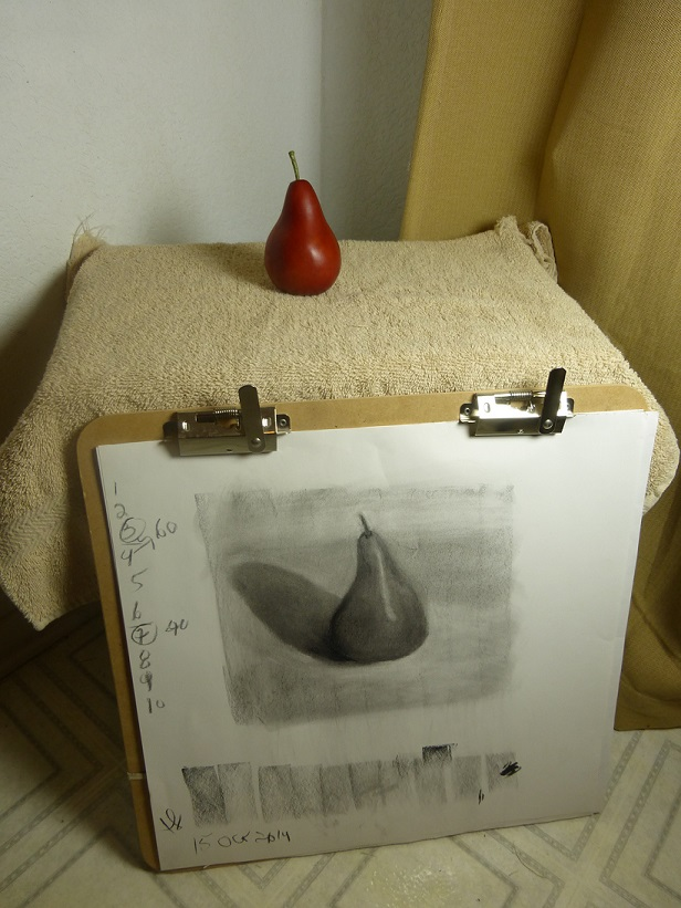 The red pear and sketch together in a photograph.  The sketch mostly looks like the red pear, but not totally.