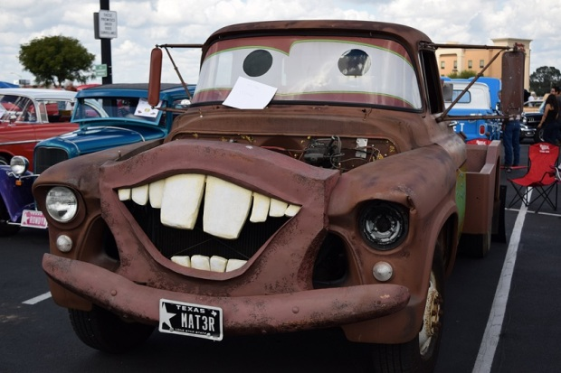 A pick up truck altered so that the front grill looks like a wide open mouth, with buck teeth