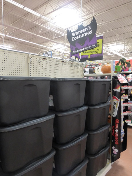 "A large display of big, black plastic tubs and above them a sign that reads ""Women's Costumes"""