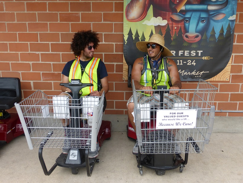 Two grocery store employees sitting on motorized carts chatting with each other