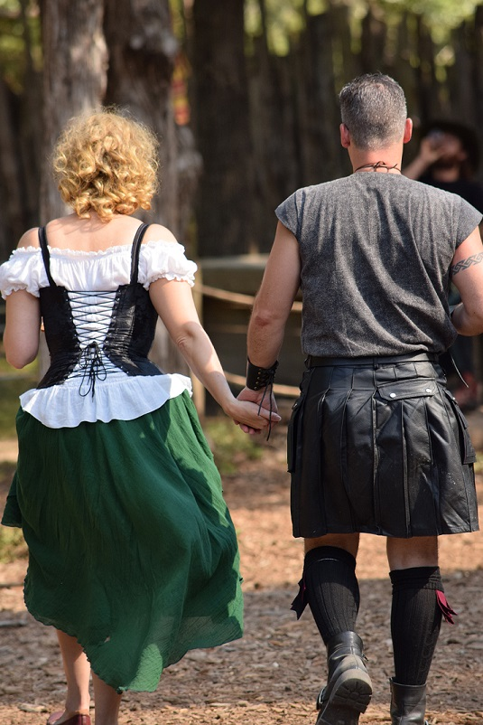Two people dressed in Celtic clothes, walking hand in hand, seen from the back