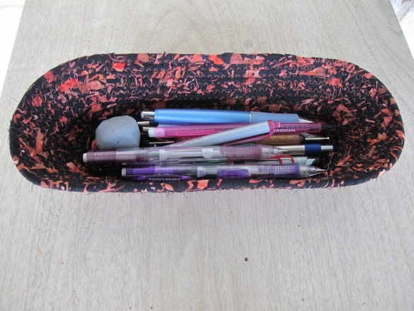 Bowl with pens, pencils, and eraser