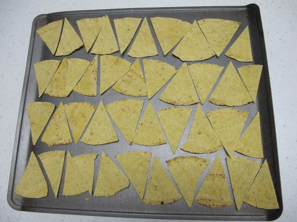 A cookie tray filled with cut up corn tortillas ready to go in the oven, to make my own corn chips
