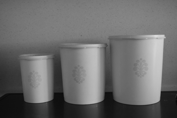 A Tupperware canister set in black and white