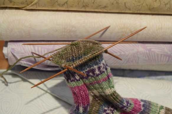The top of the sock with the four knitting needles