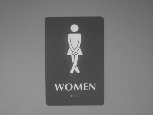 Sign to a women's bathroom with the image of a woman crossing her legs, trying not to go to the bathroom before she gets inside