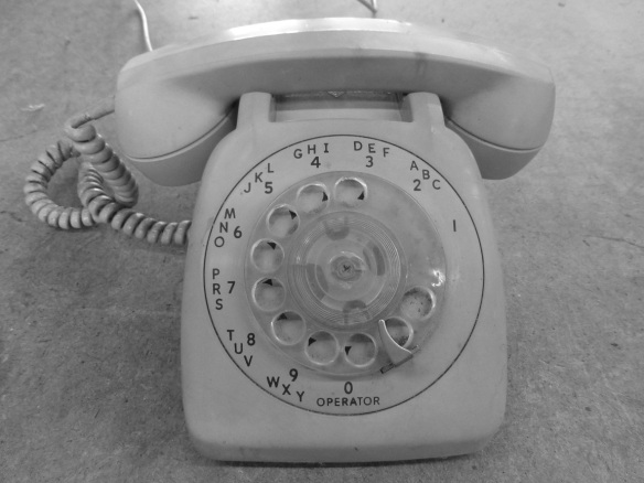 An old, rotary phone in a black and white photo