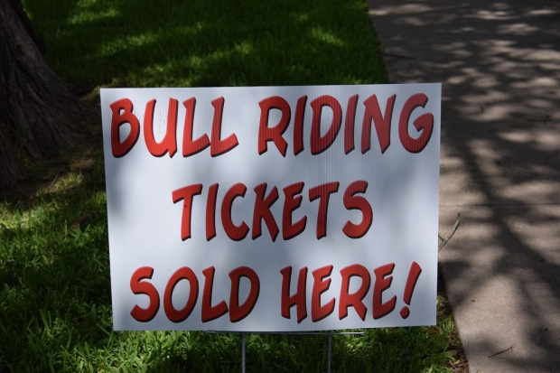 """Sign that reads """"Bull riding tickets sold here!"""""""