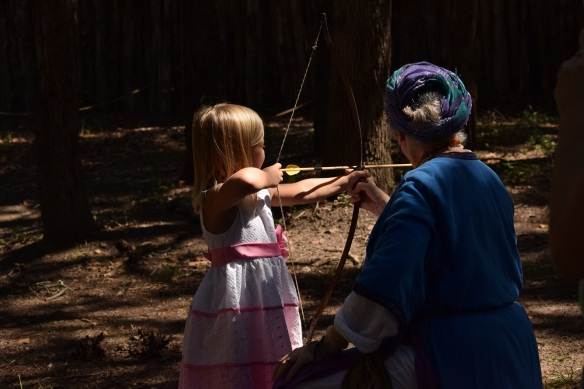 A young girl notching her bow and aiming her arrow