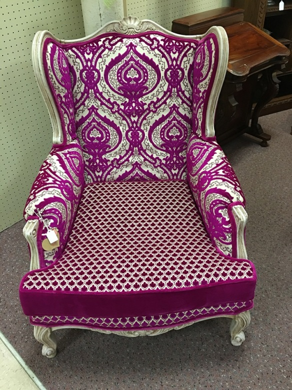A wing back chair with fabrics all with a fuchsia hue.