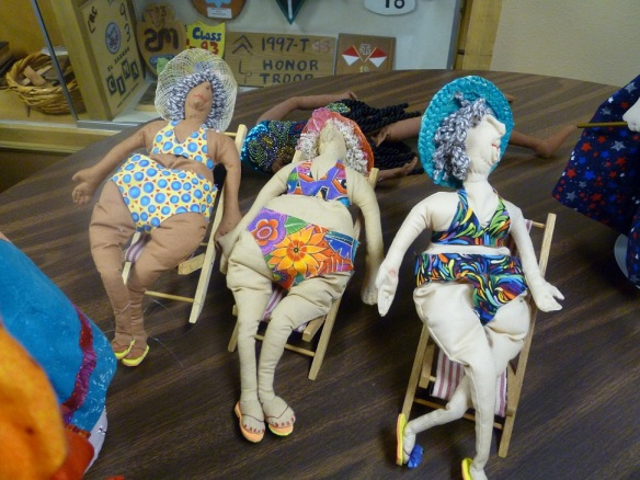 Three dolls of old women in bathing suits sitting in lawn chairs